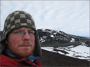 Photo of a man wearing glasses and a knit cap close to the camera, with three wind turbines on a brown dirt, and white snow hill behind him.