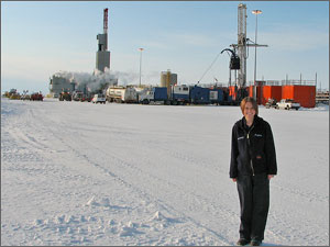 Woman standing on a snow-covered field with oil wells and machinery behind her.