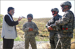 In this photo, an Afghan elder with a gray beard talks to three American soldiers on a dusty gravel road, while a U.S. military truck appears in the background atop a hill.