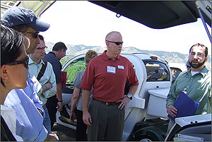 This photo shows Lt. Col. Brian Stevens and other NREL Energy Execs looking at a car while listening to a talk.