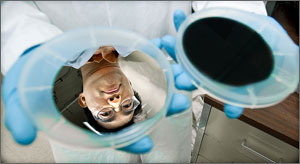 In a photo, a scientist's face is reflected on a silver-colored wafer the size of a compact disc.