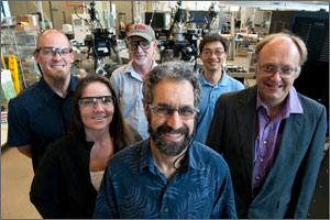 In a photo, six scientists pose in front of laboratory equipment.