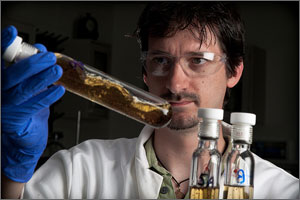 Photo of a man holding a test tube with brown liquid.
