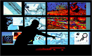 Photo of a man in shadow, standing in front of a large bank of monitors with colorful images.