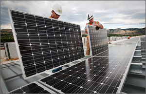 Photo of two men installing solar panels on a roof with the Colorado Front Range mountains in the background