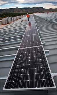 Photo of a man walking along a very long row solar panels on a roof with the Colorado Front Range mountains in the background.