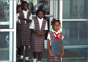 Photo shows four girls in purple-and-white uniforms walking through the entrance at Langston Hughes Charter Academy. Glass-plated walls are on either side of them.