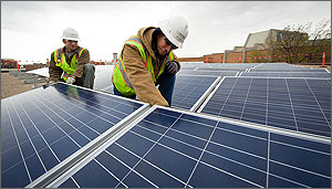 Photo of two men on a roof installing solar panels.
