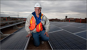Photo of a man kneeling on a roof covered in solar panels.