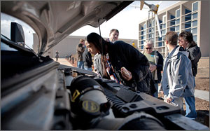 Photo of a person examining the engine on NREL's hydrogen shuttle bus.