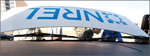 Photo of a vehicle hood propped in the air with the NREL logo and people looking under the hood.