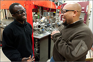 In a photo, the two scientists are wearing protective glasses and sharing a laugh in front of a pulsed-laser instrument.