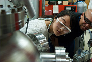 In a photo, the two scientists are wearing protective glasses, hunched over and peering into the window of a stainless-steel instrument.