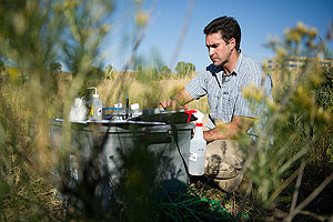 In a photo, NREL researcher Lee Elliott kneelsat his mobile lab, which is a plastic tub the size of a large picnic cooler. Atop the tub are a variety of filters, beakers and other instruments.