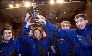Photo of a team of young men in blue jackets with the NREL logo holding a trophy over their heads.