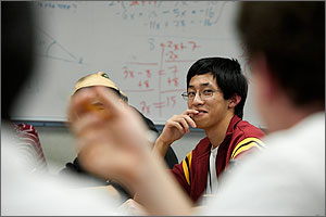 Photo of a student looking at another student in a classroom setting.