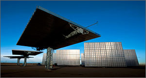 This photo shows eight Amonix 7700 solar power generators, those in front tilted horizontally, those in the rear tilted near vertically. Each is a huge rectangle divided into hundreds of squares holding cells and lenses.