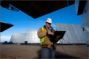 In this photo, a man in an orange safety vest and hardhat is using a laptop, with large concentrated photovoltaic generators in the background.