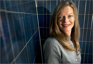 Close-up photo of NREL's Martha Symko-Davies in front of blue-tinted solar panels.