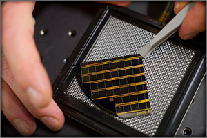 This photo shows a man's fingers, one hand holding a square solar wafer, the other holding tweezers, which are prying the wafer away from a test bed.