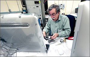 In a photo, an engineer holds a square wafer and prepares to load it into an instrument that will measure its efficiency.