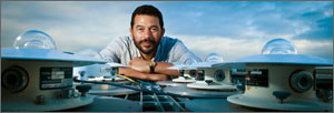 In this photo, Reda poses between two rows of solar trackers, each of which has a glass bubble top.