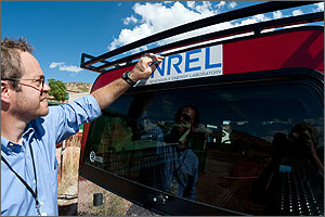 "Photo of a man placing a sticker on a car that says ""NREL."""