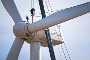 In this photo, a worker stands erect on the hub of the wind turbine near to where the blades are attached. An orange harness is wrapped around one of the blades and attached to the crane's pulley system. The man's height is approximately equal to the width of the blade.