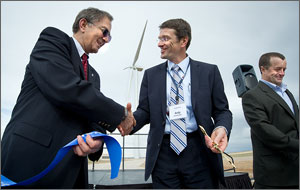 This photo shows a handshake between executives with NREL and Alstom, a section of ribbon in the foreground, and the Alstom Eco 100 wind turbine in the background.
