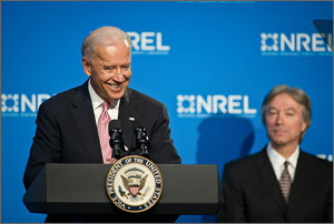Photo of a US Vice President Joe Biden in front of a blue and white background that says NREL with a man seated on a stool behind him.