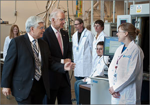 Photo of a US Vice President Joe Biden with NREL Director Dan Arvizu in a Lab with NREL staff looking on.