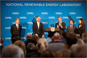 Photo shows VIPs on the speaker platform, with the blue-and-white NREL logo in the background.
