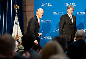 Photo shows a smiling Joe Biden approaching the NREL podium as a man in a suit awaits him. In the background is a blue and white sign with NREL logos on it.