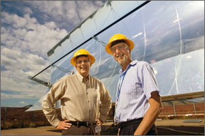Two men in hard hats stand in front of a shiny, curved solar collector