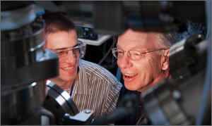 In this photo, the two scientists are smiling as they peer at instruments that process and measure solar cells.