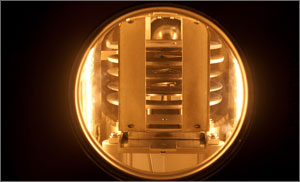 This is a close-up of stacked plates in the molecular beam epitaxy reactor, shining gold in intense light.