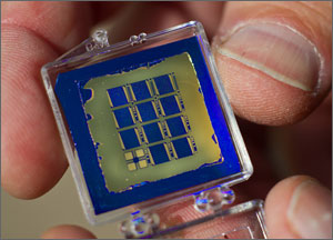 This is a close-up of a wafer holding 11 bluish solar cells. Olson's thumbs and forefingers are holding the wafer which is about an inch square.