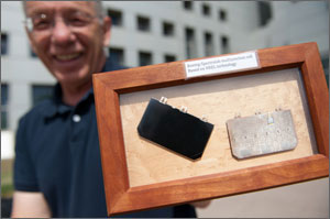 In this photo, Olson holds a wooden frame encasing two of the earliest multi-junction cells, one black, one white, and both several times larger than today's models.