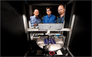 In this photo, three scientists are peering inside an instrument that has in its center what looks like a turntable holding a bright blue wafer.