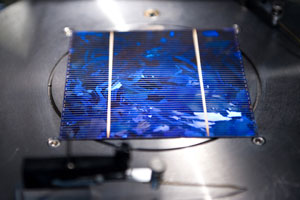 This is a close-up of a solar cell, resting on a stainless steel disc. The wafer is square, blue and richly textured.