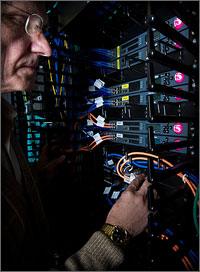 Photo of a man hooking up cables on the back of a computer rack.