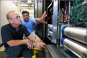 In this photo, two scientists are squatting in front of the power block, looking at the insides, which include four large silver cylinders and a digital controller that looks like a green circuit board.