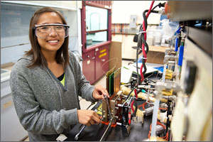 Photo of Amy Tsang in a lab near a hydrogen fuel cell membrane.
