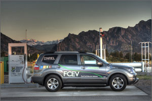 Photo of an SUV vehicle in front of a fueling station with mountains in the background.