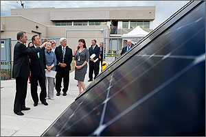 Photo of a man gesturing as he explains the solar panels in front of him to others to his left.