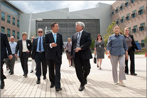 Two men in suits walking toward the camera are talking and gesturing. Several other people are following them.
