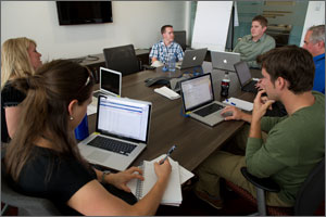 In this photo, six NREL employees sit around a large brown table, all with their laptops open.