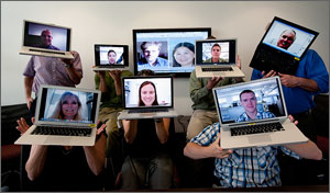 In this photo, six researchers playfully hold up laptops in front of their faces. Each laptop has a photo of the face of the person holding it.