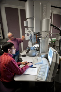 In this photo, scientist Kim Jones is standing, using an up-reached hand to make a point to scientist Yanfa Yan. Jones is standing in front of an ion beam electron microscope which is taller than he is.