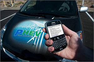 Photo of man's hand holding a mobile device with a plug-in hybrid electric vehicle in the background.